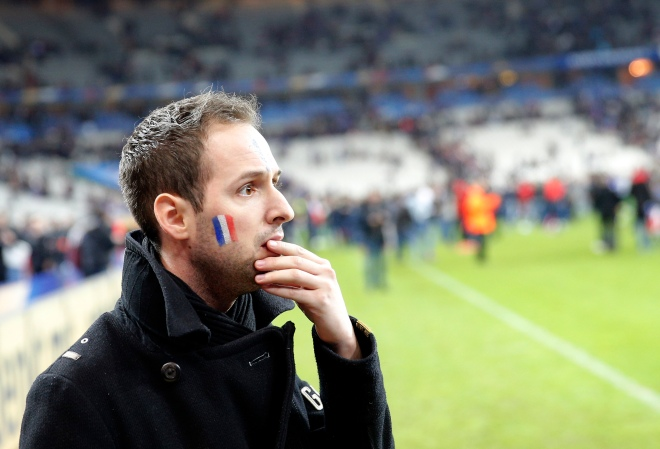 A French supporter reacts after invading the pitch of the Stade de France stadium at the end of the international friendly soccer match between France and Germany in Saint Denis, outside Paris, Friday, Nov. 13, 2015. Hundreds of people spilled onto the field of the Stade de France stadium after explosions were heard nearby. French President Francois Hollande says he is closing the country's borders and declaring a state of emergency after several dozen people were killed in a series of unprecedented terrorist attacks. (AP Photo/Christophe Ena)