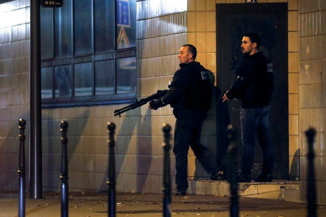 epa05023917 French police officers take cover while on the lookout for the shooters who attacked the restaurant 'Le Petit Cambodge' earlier tonight in Paris, France, 13 November 2015. At least 60 people have been killed in a series of attacks in the French capital Paris, with a hostage-taking also reported at a concert hall. EPA/ETIENNE LAURENT